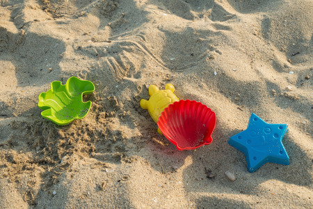 Sandy beach with colorful sand molds of sea creatures. Imagens