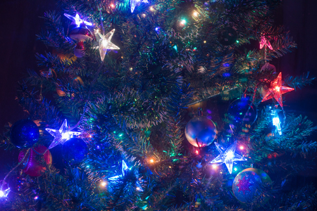 Beautiful Christmas tree decorated with traditional baubles and shiny rainbow stars, dark background.