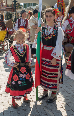 Varna, Bulgaria - April 28, 2018: Participants of the annual Varna Spring Carnival. Two cute girls in folk costumes.