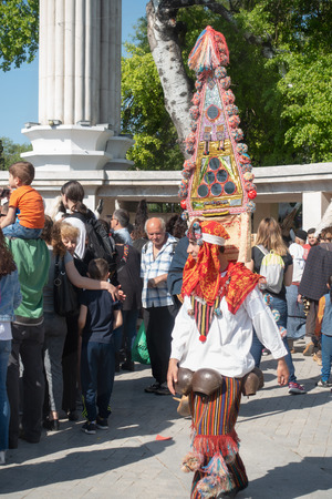 Varna, Bulgaria - April 28, 2018: Participant of the annual Varna Spring Carnival walk the street in his colorful kukeri costume with hight hat and large bells attached to his belt.