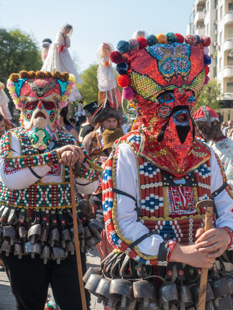 Varna, Bulgaria - April 28, 2018: Two participants of the annual Varna Spring Carnival dressed in traditional kukeri costumes