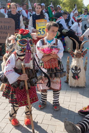 Varna, Bulgaria - April 28, 2018: Two young participants of the annual Varna Spring Carnival in their beautiful kukeri costumes. Редакционное
