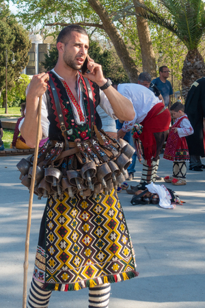Varna, Bulgaria - April 28, 2018: Participants of the annual Varna Spring Carnival. Man in traditional kukeri costume with many bells attached to his belt talks on a mobile phone.