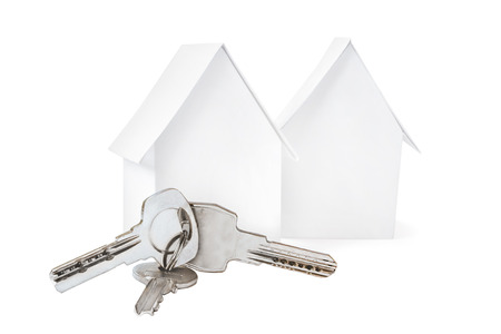 Two small toy houses and keys, isolated on white background.