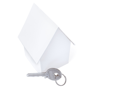 Small white toy house and a key isolated on white copy space background.