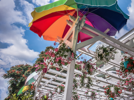 Street cafe summer terrace fragment: rainbow parasol and beautiful flowers against the blue sky. Varna, Bulgaria, Black Sea coast.