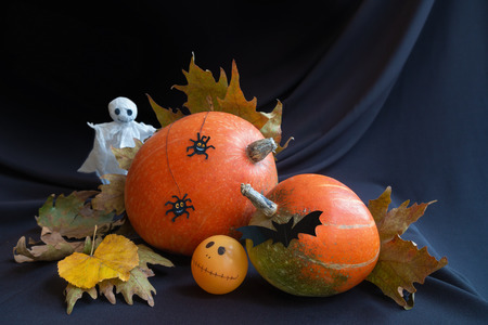 Halloween pumpkins decorated with paper ghost, spooky spiders, bat and autumn leaves, dark background.