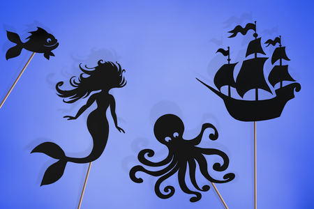 Shadow puppets of mermaid, kraken, sailing ship, fish and sea horse, isolated on white background. Imagens