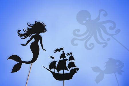 Shadow puppets of mermaid and sailing ship and shadows of sea creatures. Little mermaid storytelling.