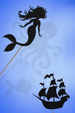 Shadow puppets of mermaid and sailing ship and shadows of kraken and deep sea fish.