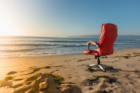 Old red office chair on the beach at sunrise, copy space background Imagens