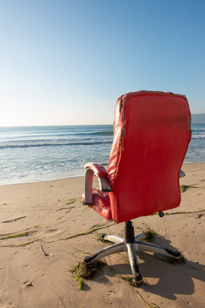 Old red office chair on the sea beach, vertical, copy space background