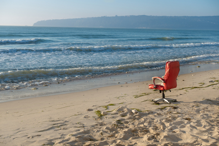 Empty office chair on the deserted beach, copy space background.