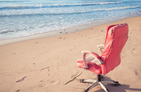 Old pink office chair on the beach,  pastel colors, copy space background.