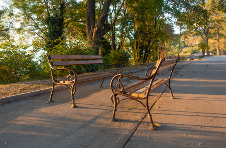 Two park benches in golden morning sunlight, autumn background. Imagens
