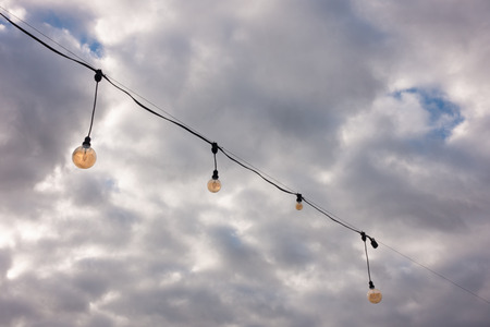 String of orange light bulb decoration against cloudy sky. Imagens - 112441254