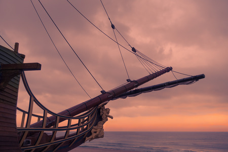 Galleon sailing ship bow with angel figurehead against sunset sky.