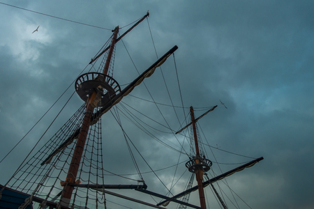 Galleon sailing ship masts and rigging against storm cloudy sky, copy space background.