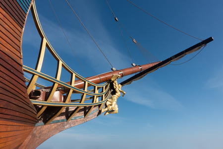 Galleon sailing ship bow with angel figurehead against blue sky.