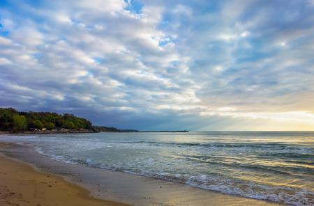 Cloudy sunrise at a deserted seashore, seascape natural background.