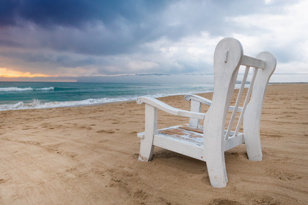 Empty armchair on the deserted beach before the storm, copy space background. Stock Photo - 125107777