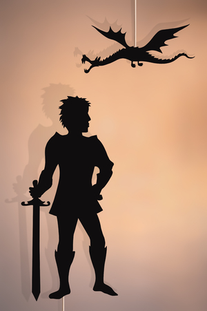 Shadow puppets of knight and flying dragon, copy space background. Stock Photo - 125107784