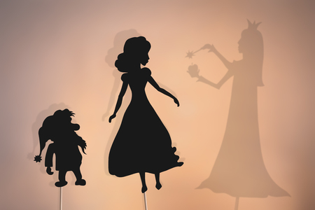 Shadow puppets of Snow White and a dwarf and Evil Queens shadow. Snow White and the Seven Dwarfs storytelling.