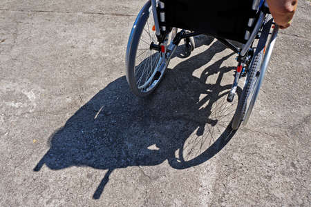 Disabled old woman on a wheelchair and shadow