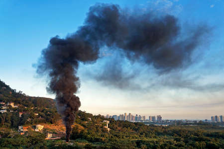 A huge black column of smoke in abandoned ground