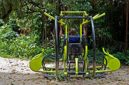 Black man exercising on public gym equipment at