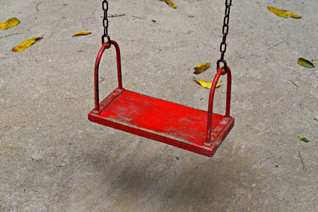 Red wooden swing hanging on chains Archivio Fotografico