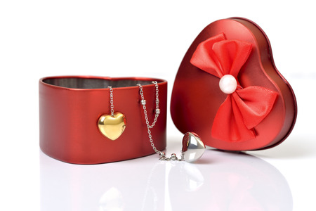 Red heart gift box and heart necklace on white   photo
