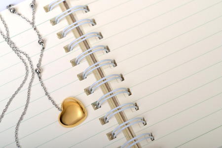 diary: A golden heart necklace on a empty page of diary