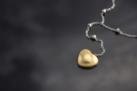 Golden heart with necklace chain on black    photo