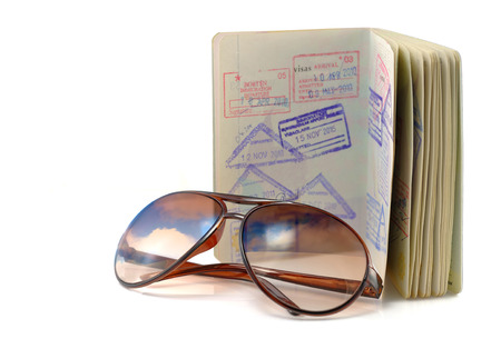 Journal, passport and sunglasses on white.
