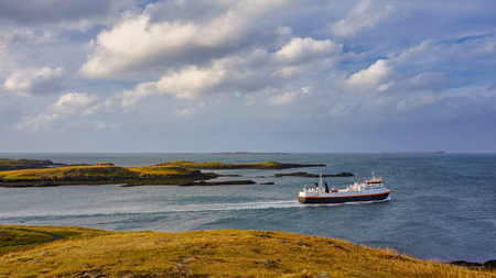 Ferry leaving from Port Baldur in Stykkisholmur and head to   in northern fjord of Iceland with cloudy sky above.