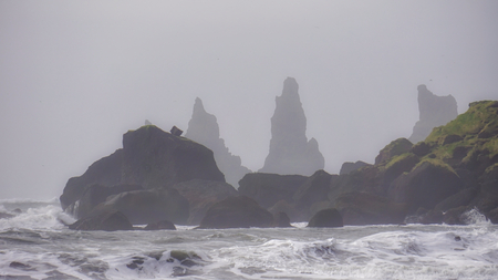 The Misty day morning at Reynisdrangar the volcanic rock formations at Reynisfjara black sand beach. Coast of the Atlantic ocean near Vik, southern Iceland.