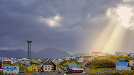 Beautiful traditional houses in Stykkisholmur the harbour village with cloudy sky and sun ray to the village , Iceland.