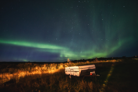 The supernatural northern aurora light in the meadow at camp ground near thingvellir national park Iceland.