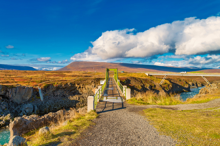 The steel bridge across the river that stream from Godafoss waterfall with blue sky in Iceland. Reklamní fotografie