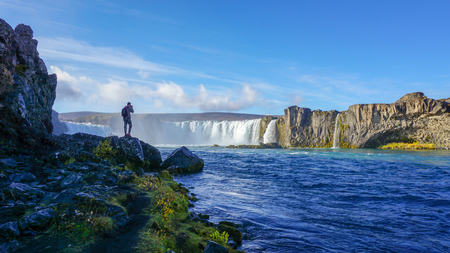 A tourist enjoy viewing and snap a photo at Godafoss the huge waterfalls. One of most famous place in Iceland