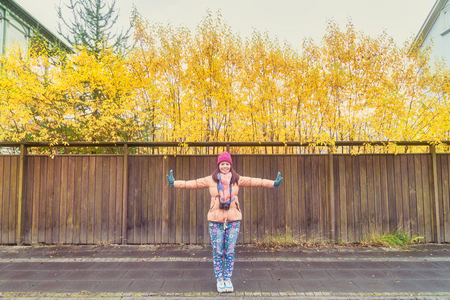 A woman happy tourist and post an action for take a photo with wooden wall and yellow leaves autumn color background in Akureyri city of Iceland.