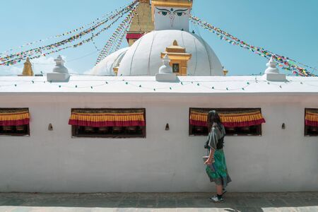 An asian women tourist touch the bell inside the wall of Boudhanath Stupa and praying get blessing at Kathmandu, Nepal.