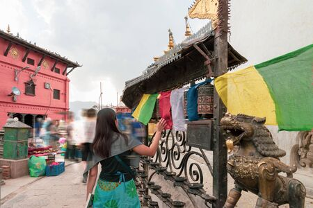 Tibetan prayer wheels. A woman tourist rolling the prayer wheels at Swayambhunath, Nepal. Text translation: The magic symbol power of buddhism for prayer get divine blessings and good fortune