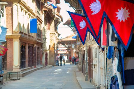 The Nepal national flag in foreground decoration in front of nepali house and the background is perspective of village in Kathmandu Nepal.