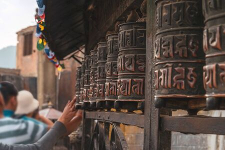 Tibetan prayer wheels at Swayambhunath, Nepal. Text translation: The magic symbol power of buddhism for prayer get divine blessings and good fortune.
