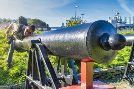 Crazy man tourist have fun with the vintage canon that located in the garden of Bergenhus Fortress, Bergen, Norway 版權商用圖片
