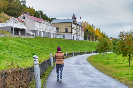 A traveler woman walking on the street for sightseeing, beautiful perspective view in Akureyri, Iceland Stok Fotoğraf