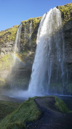 Seljalandsfoss huge waterfall in Iceland in sunny day with rainbow and blue sky in summer. Stok Fotoğraf