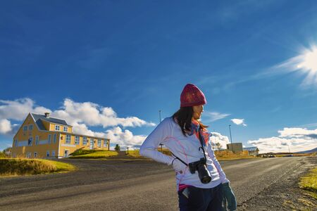 A traveler woman walking on the street for sightseeing the typical Icelandic landscape with houses and beautiful blue sky background, Iceland